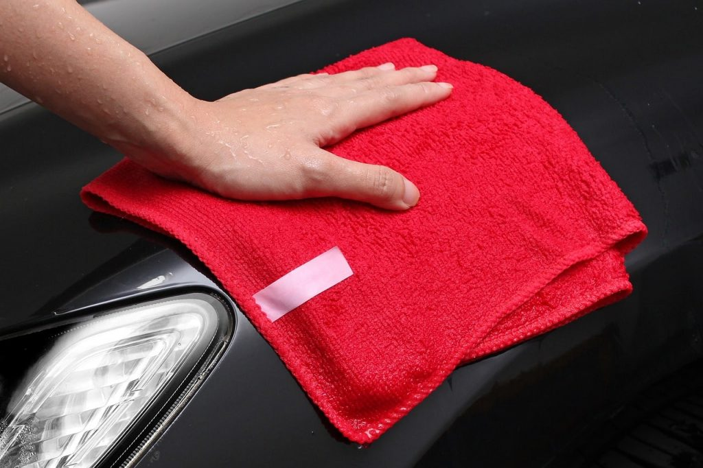 Red microfiber cloth cleaning black car